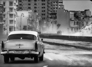 Car Driving Along Road WIth Wave Crashing in Havana